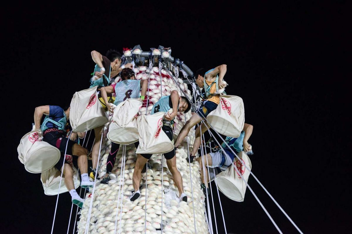 Competitors take part in a scramble up an 18-metre tower made from imitation buns during the annual Cheung Chau bun festival in Hong Kong, shortly after midnight on May 4, 2017.