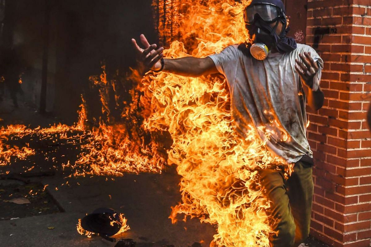 A demonstrator catches fire, after the gas tank of a police motorbike exploded, during clashes in a protest against Venezuelan President Nicolas Maduro, in Caracas on May 3, 2017.
