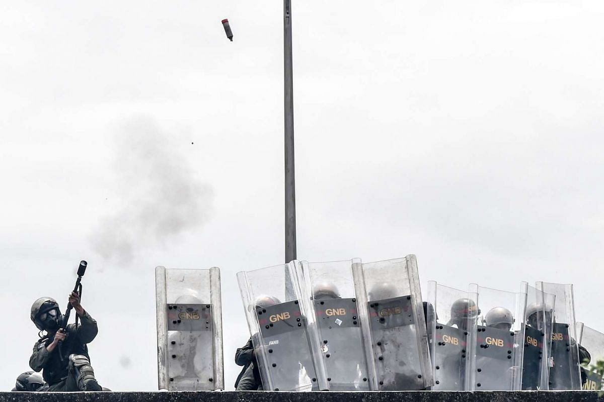 National Guard personnel in riot gear fire tear gas grenades and throw gas canisters at opposition demonstrators protesting against Venezuelan President Nicolas Maduro, in Caracas on May 3, 2017.