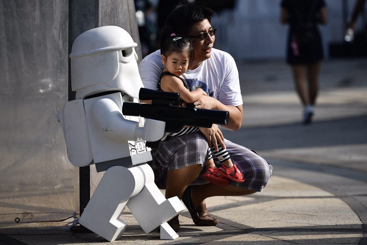 Mr Argus Tong and his daughter Arwen taking a photo with a Snow trooper figurine.