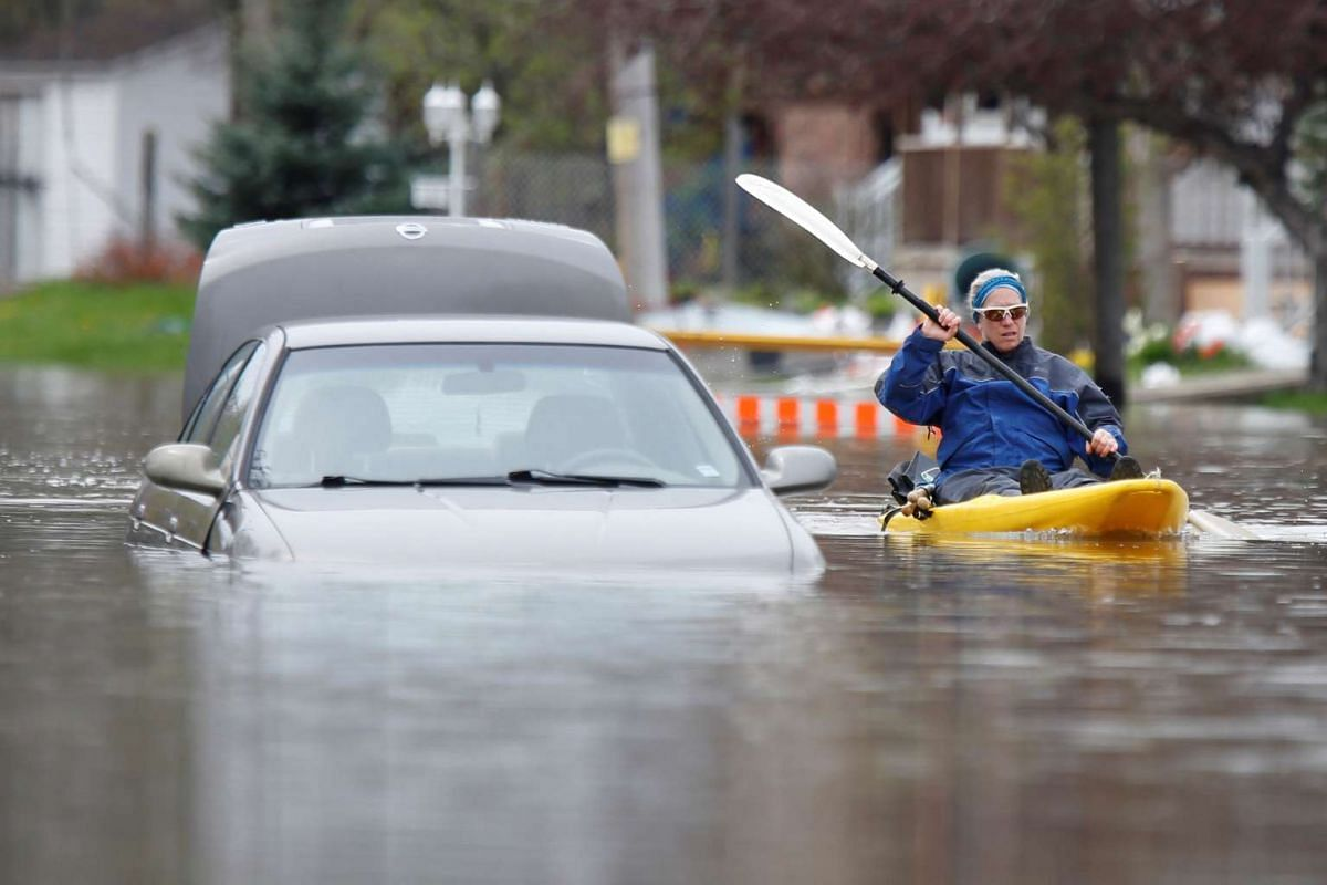 A woman paddles a kayak past an abandoned car on a flooded residential street in Gatineau, Quebec, Canada, May 4, 2017.