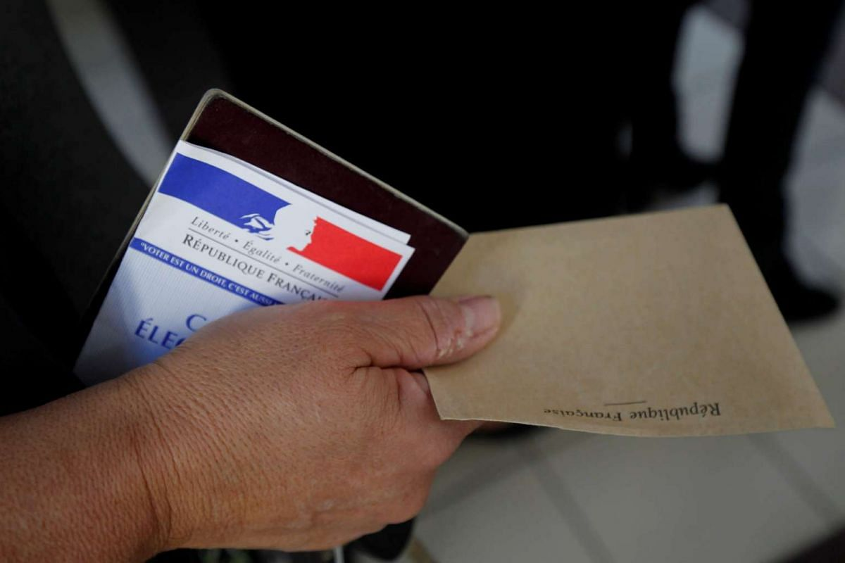 A French citizen holding a ballot as polling booths open in Marseille, on May 7, 2017.