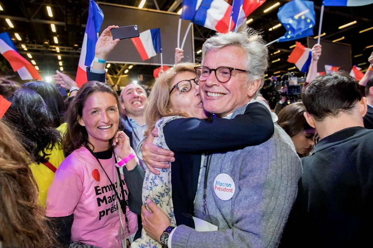 Supporters of Mr Emmanuel Macron react as results for the first round of the French presidential election are projected at the En Marche headquarters in the Parc des Expositions in Paris, France, on April 23, 2017.