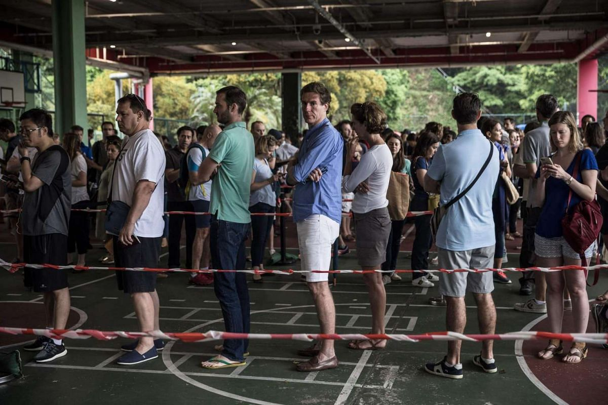 People wait to register at a polling station during the second round of France's presidential election in Hong Kong on May 7, 2017.