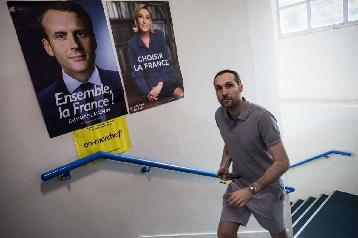 A man walks past posters of France's presidential election candidates Marine Le Pen and Emmanuel Macron at a polling station during the second round of France's presidential election in Hong Kong on May 7, 2017.