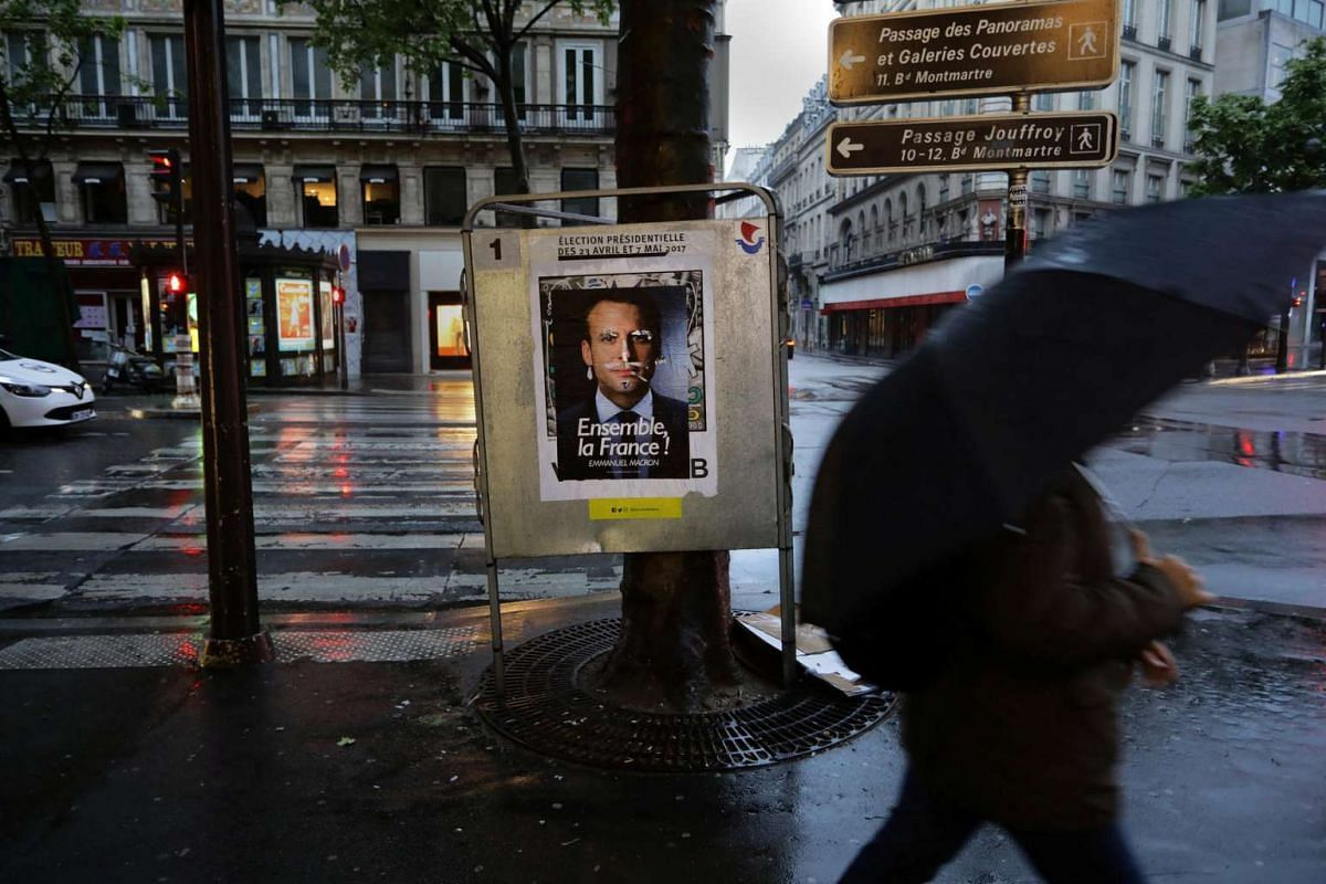 A man walks past an election poster of candidate Emmanuel Macron on the day of the French presidential election in Paris, France, on May 7, 2017.