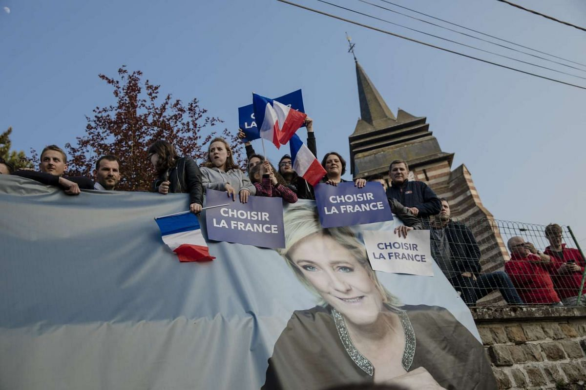 People waving French flags during Le Pen's election campaign event in Ennemain, France, on May 4, 2017.
