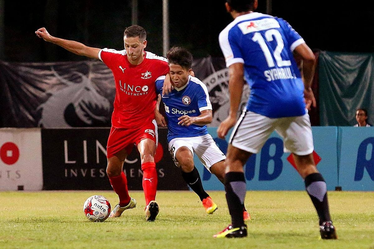 Home United's Stipe Plazibat (in red) fending off Garena Young Lions' Rusyaidi Salime during their S-League match.