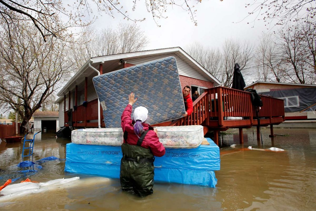 Jean-Francois Perrault (centre) and Julie Theriault (left) moving mattresses from a home in a flooded residential area in Gatineau, Quebec, Canada.