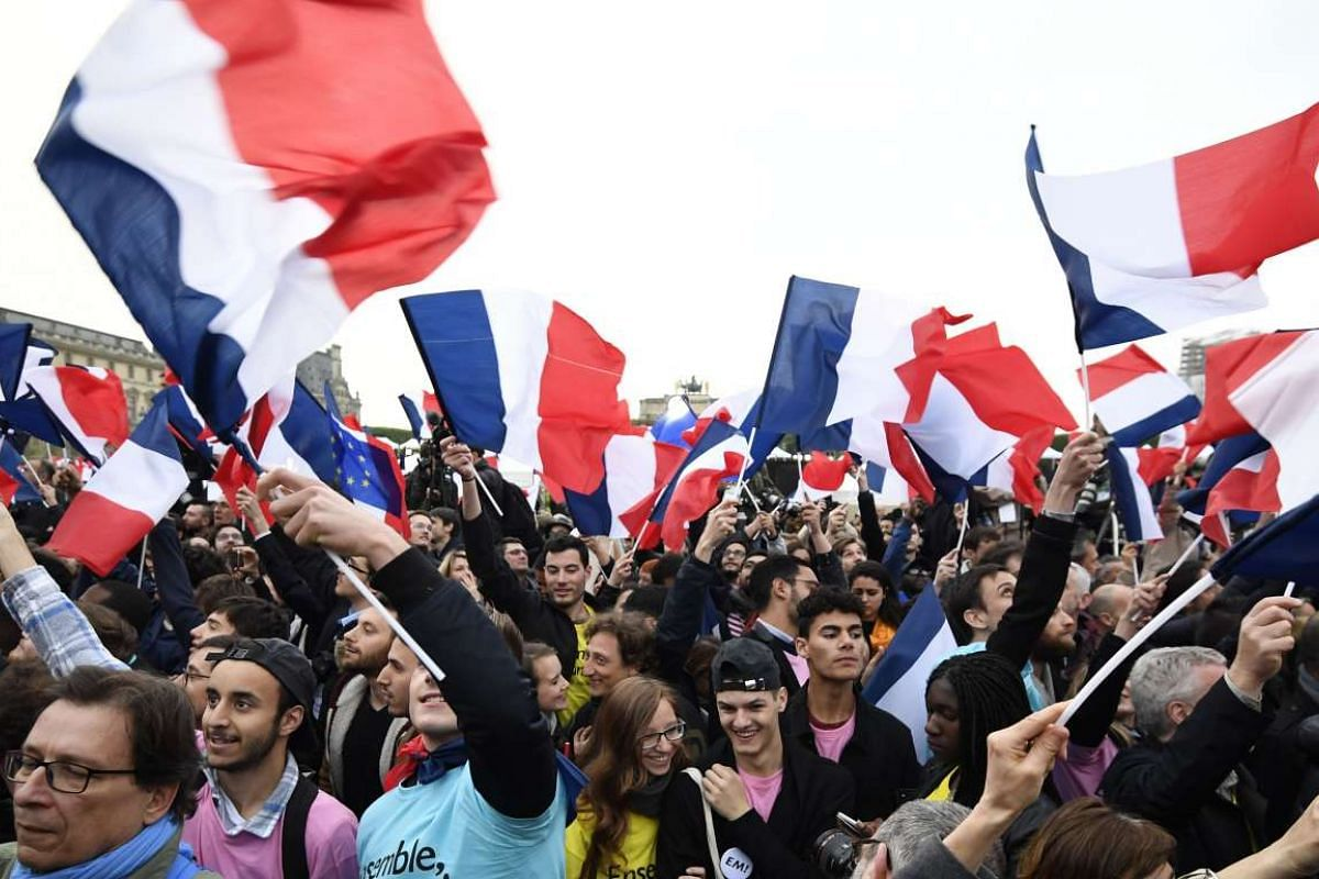 Supporters of French President-elect Emmanuel Macron celebrating in front of the Pyramid at the Louvre Museum in Paris.
