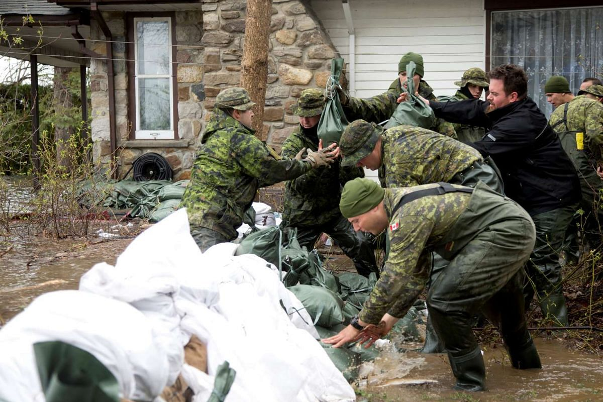 Canadian soldiers placing sandbags outside a home in a flooded residential neighbourhood in Pierrefonds, Quebec, Canada.