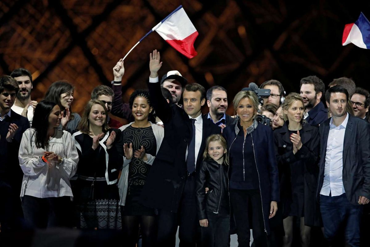 French President elect Emmanuel Macron and his wife Brigitte Trogneux celebrate on the stage at his victory rally near the Louvre in Paris, France May 7, 2017