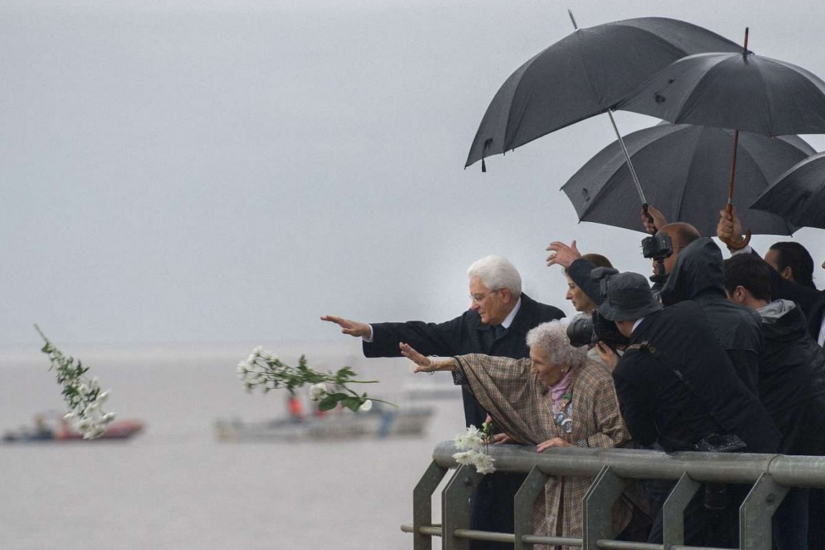 "Italian President Sergio Mattarella (L) alongside members of the human rights organization Madres de Plaza de Mayo throws flowers into the Rio de la Plata river to pay homage to the victims of Argentina's dictatorship (1976-1983) at the ""Parque de la"