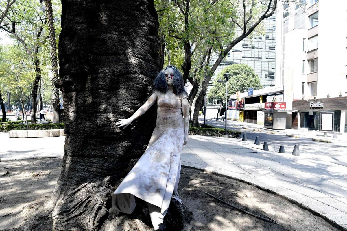 "An activist wearing white veils and with blood stains in her dress participates in a performance called ""Las 43 Lloronas"" in solidarity with the mothers of 43 missing students from the Ayotzinapa rural teachers school in Mexico City on May 7, 2017. O"