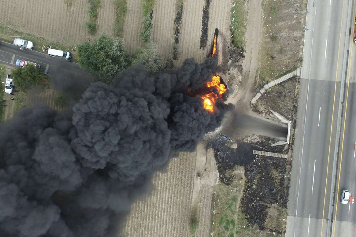 Aerial view taken from a drone showing the flames generated by a fire in a clandestine fuel valve in Santa María Nenetzintla, Amozoc, Puebla on May 7, 2017. The theft of fuel has put the war in several states of central Mexico, with violent clashes