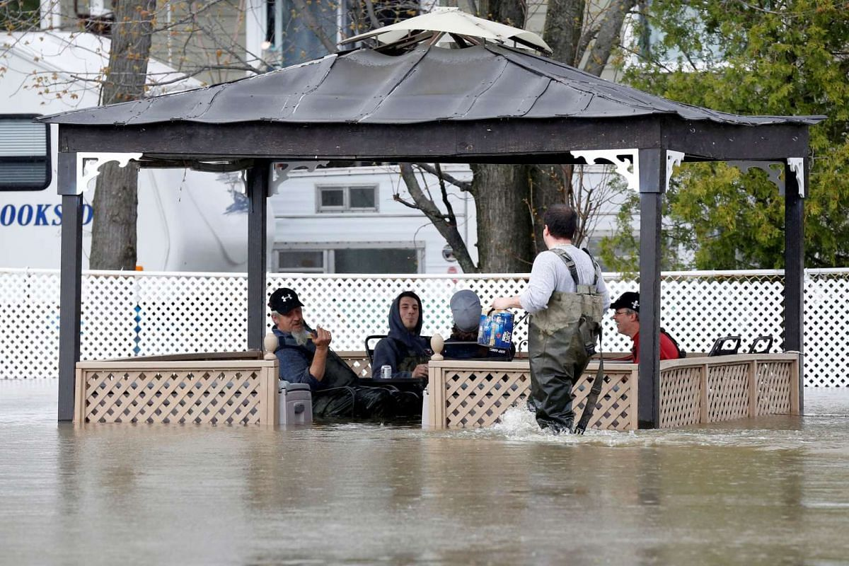 Residents drinking beer while sitting in a flooded gazebo in Rigaud, Quebec, Canada.