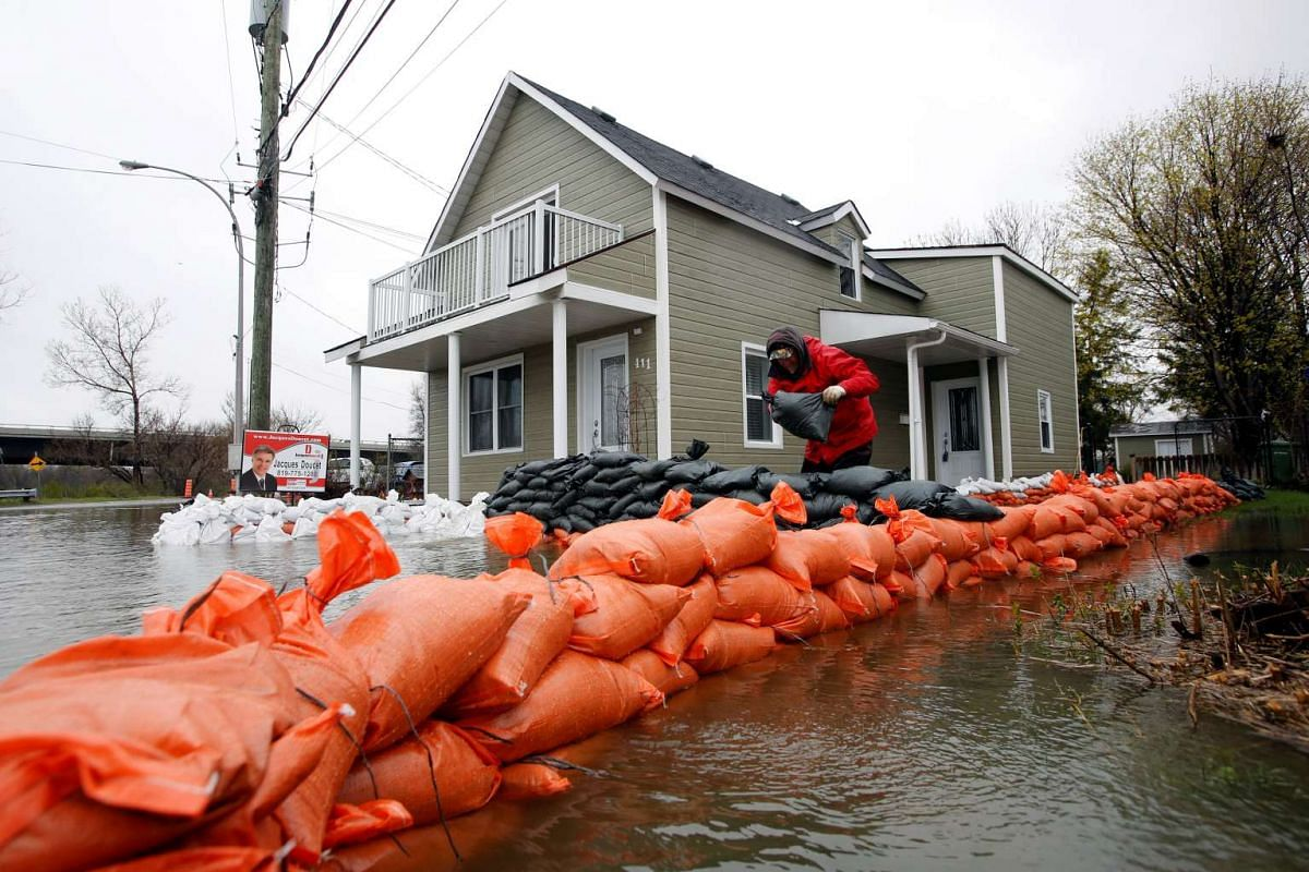 A man placing sandbags outside a home in a flooded residential area in Gatineau, Quebec, Canada.