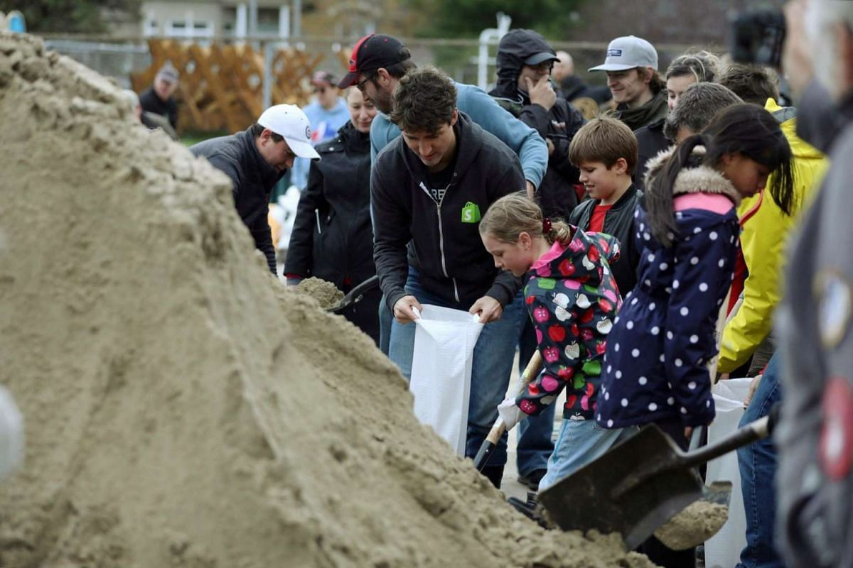 Canada's Prime Minister Justin Trudeau (centre) helping to fill sandbags after a flooding in Terrasse-Vaudreuil, Quebec, Canada.