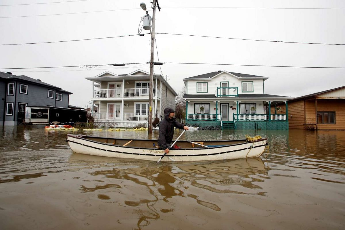 A man paddling a canoe in a flooded residential area in Gatineau, Quebec, Canada.