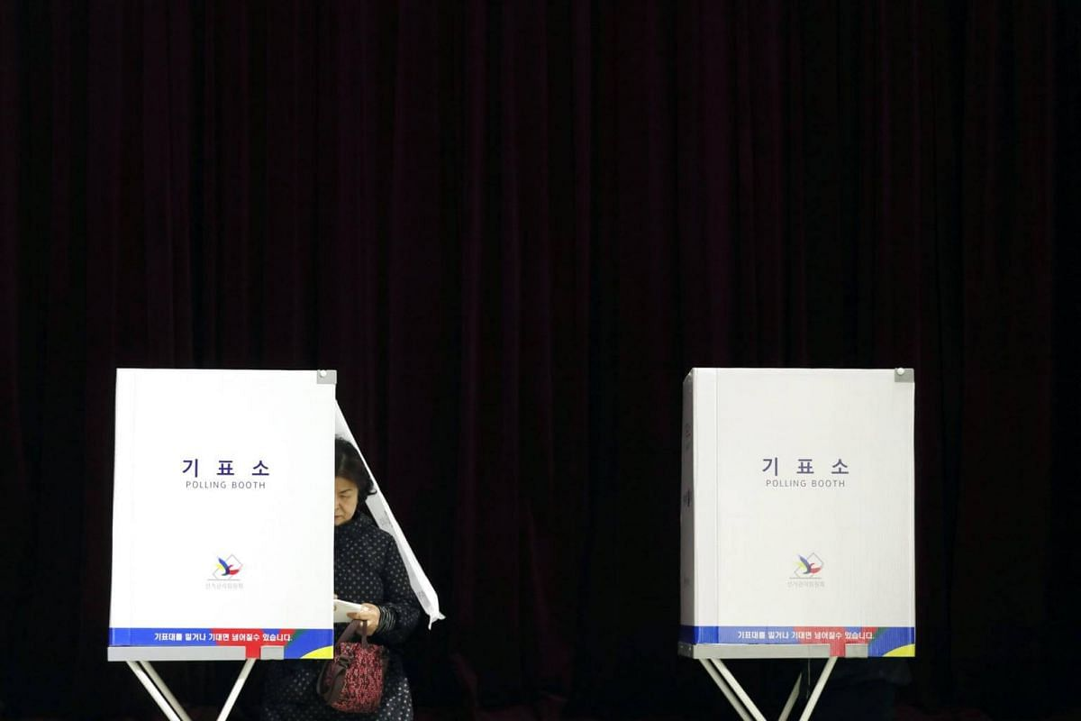 A woman comes out of a polling booth to cast her vote at a polling station in Seoul, South Korea, on May 9, 2017, as voting began across the country for the presidential election.
