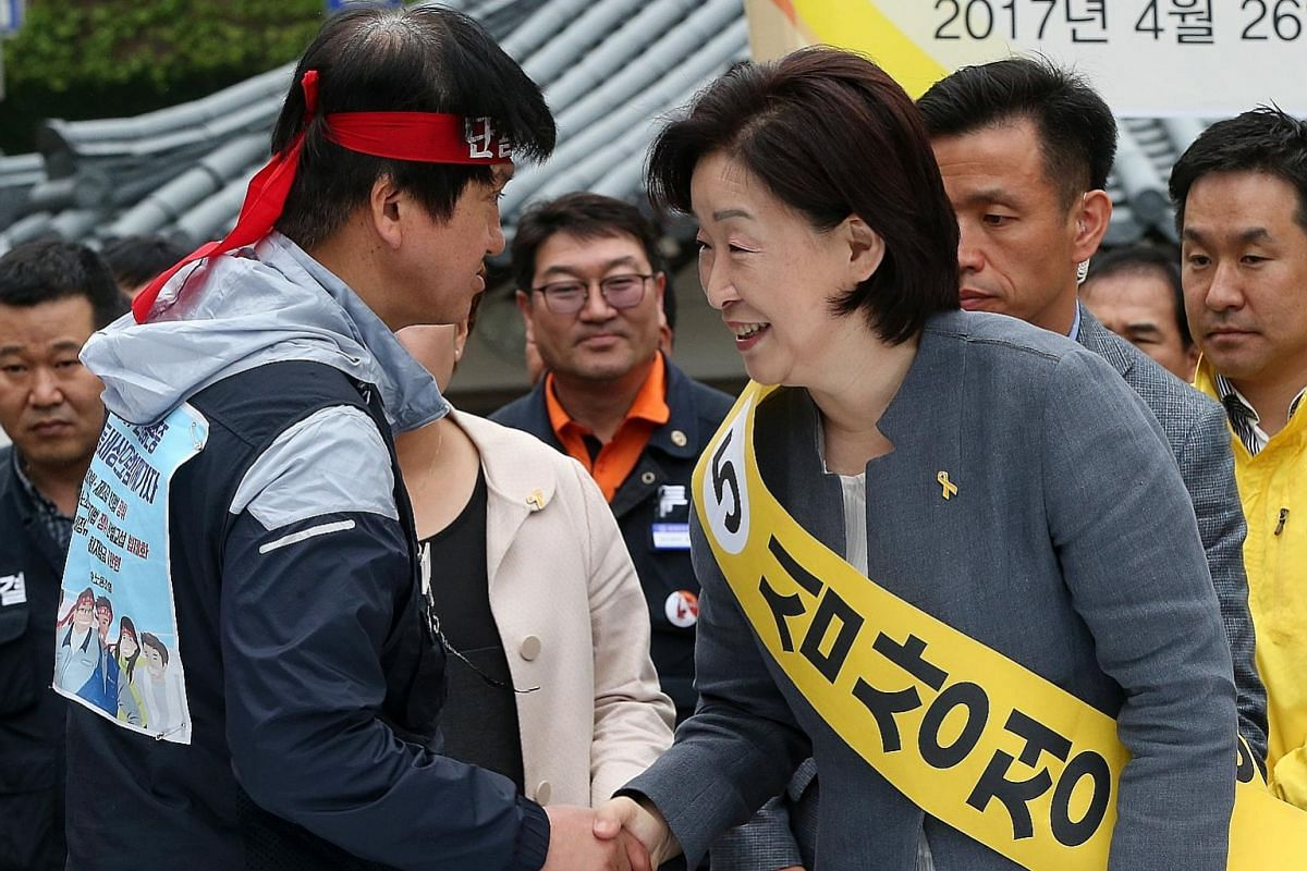 Above: Ms Sim Sang Jeung, the Justice Party's presidential candidate, greeting a union leader during a campaign stop at Hyundai Heavy Industries in the south-eastern city of Ulsan late last month. Left: A supporter of Ms Sim all set to take part in a