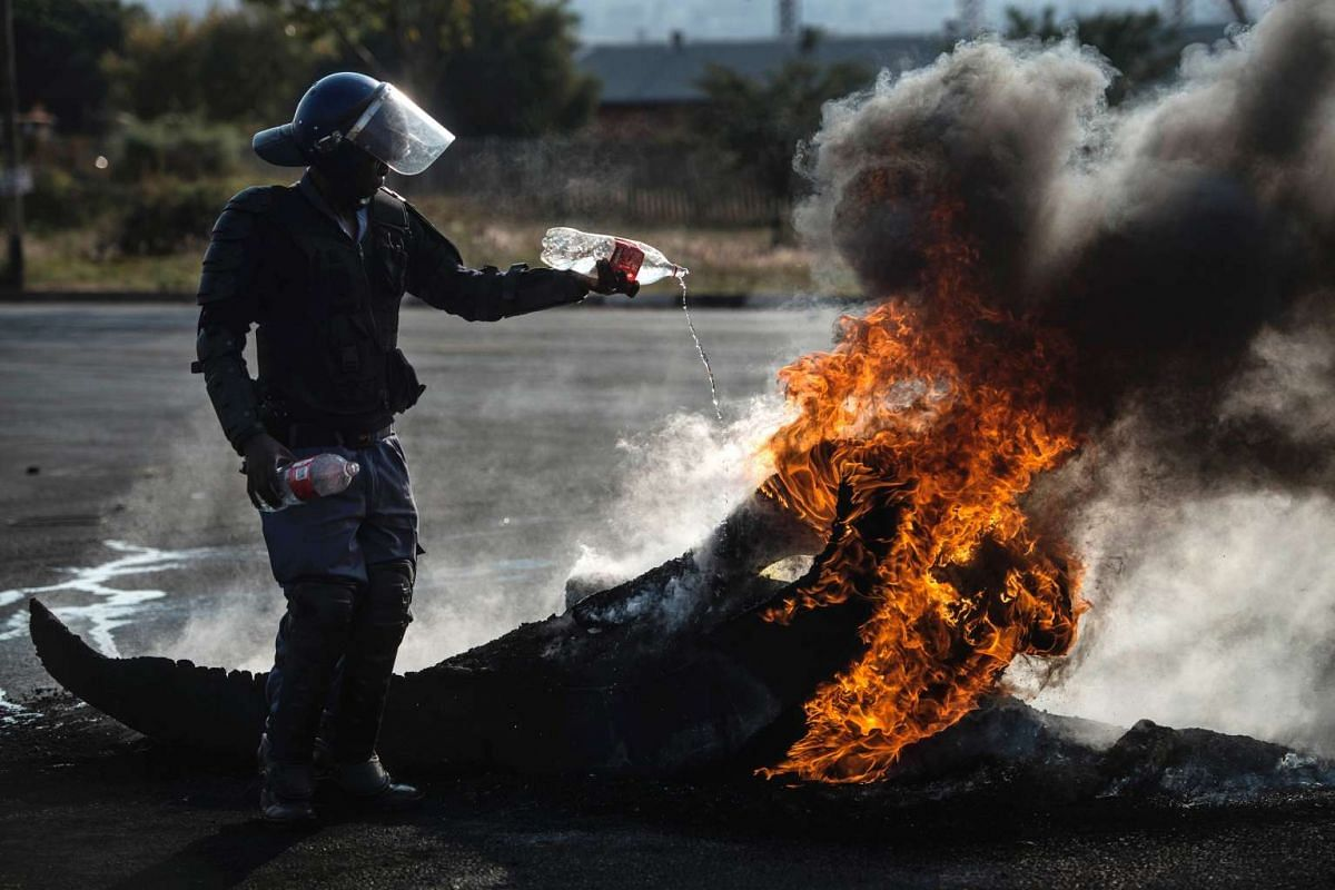 A South African policeman attempts to extinguish a fire after demonstrators burnt tyres to barricade a road, during violent protest demanding better housing on May 11, 2015 in Finetown, Ennerdale, South Africa.
