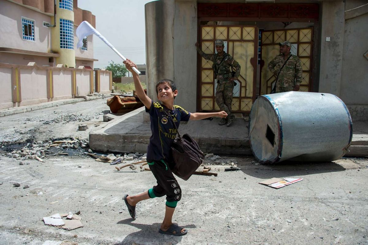 An Iraqi boy carries a white flag as he evacuates his home as Iraqi forces advance in the northwestern al-Haramat neighbourhood of Mosul on May 11, 2017, during the ongoing offensive to retake the area from Islamic State (IS) group fighters.