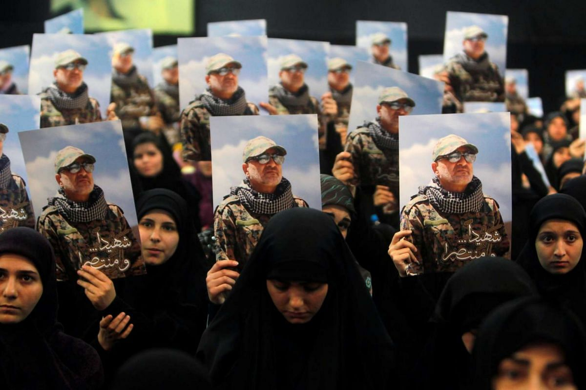 Women carry pictures of Hezbollah commander Mustafa Badreddine, who was killed in an attack in Syria, during a ceremony marking a year after his death in Beirut's southern suburbs, Lebanon May 11, 2017.