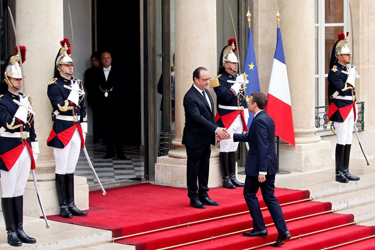 Outgoing French President Francois Hollande greeting president-elect Emmanuel Macron at the Elysee Palace in Paris on May 14, 2017.