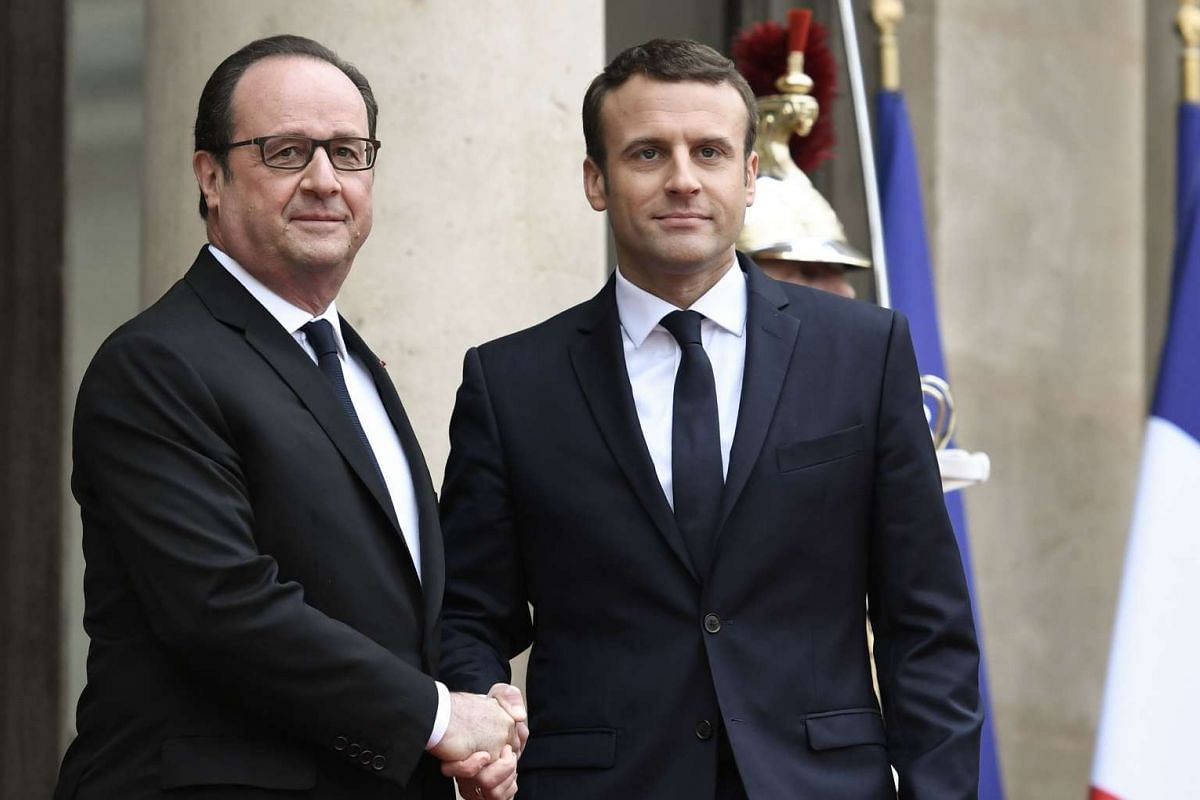 French president-elect Emmanuel Macron (right) is welcomed by his predecessor Francois Hollande as he arrives at the Elysee presidential Palace for the handover and inauguration ceremonies in Paris on May 14, 2017.