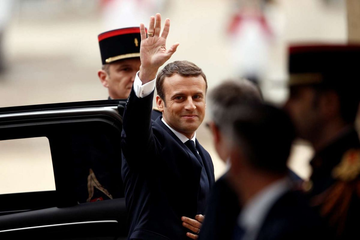 French president-elect Emmanuel Macron waving as he arrives to attend a handover ceremony with outgoing President Francois Hollande at the Elysee Palace in Paris on May 14, 2017.