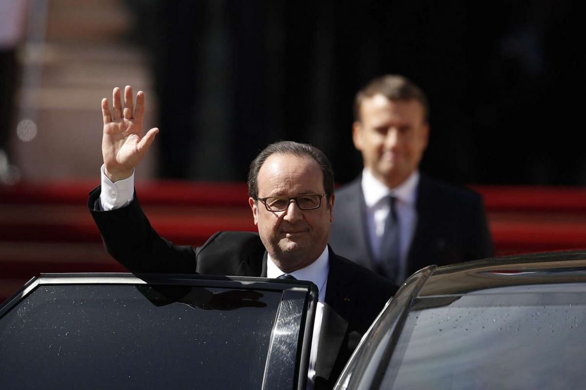 Former French president Francois Hollande waving to the crowd after handing over power to President Emmanuel Macron (background), at the Elysee Palace in Paris on May 14, 2017.