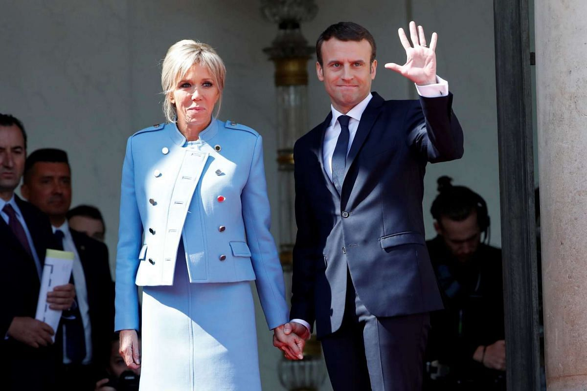 French President Emmanuel Macron and his wife Brigitte Trogneux waving to former president Francois Hollande after the handover ceremony at the Elysee Palace on May 14, 2017.