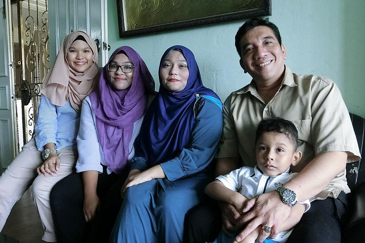 Madam Nuraida Salim (centre), with husband Muhammad Salleh Mohamed and son Akhdan Alkauthar, has grown closer to her daughers Aqilahtul Syahirah (far left) and Aqidahtul Batrisyia after she amputated her right leg.