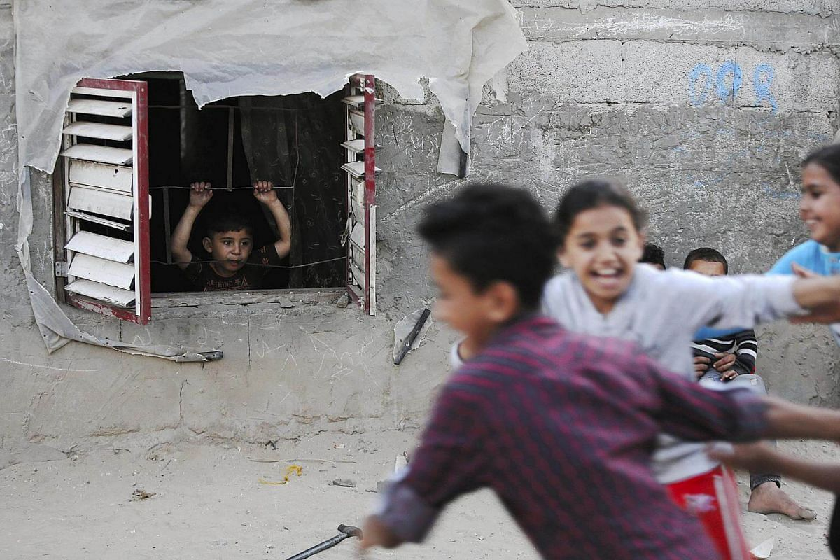 Palestinian refugee children play in the streets near their families' makeshift houses in the Khan Younis refugee camp in the southern Gaza Strip, on Wednesday (May 17).