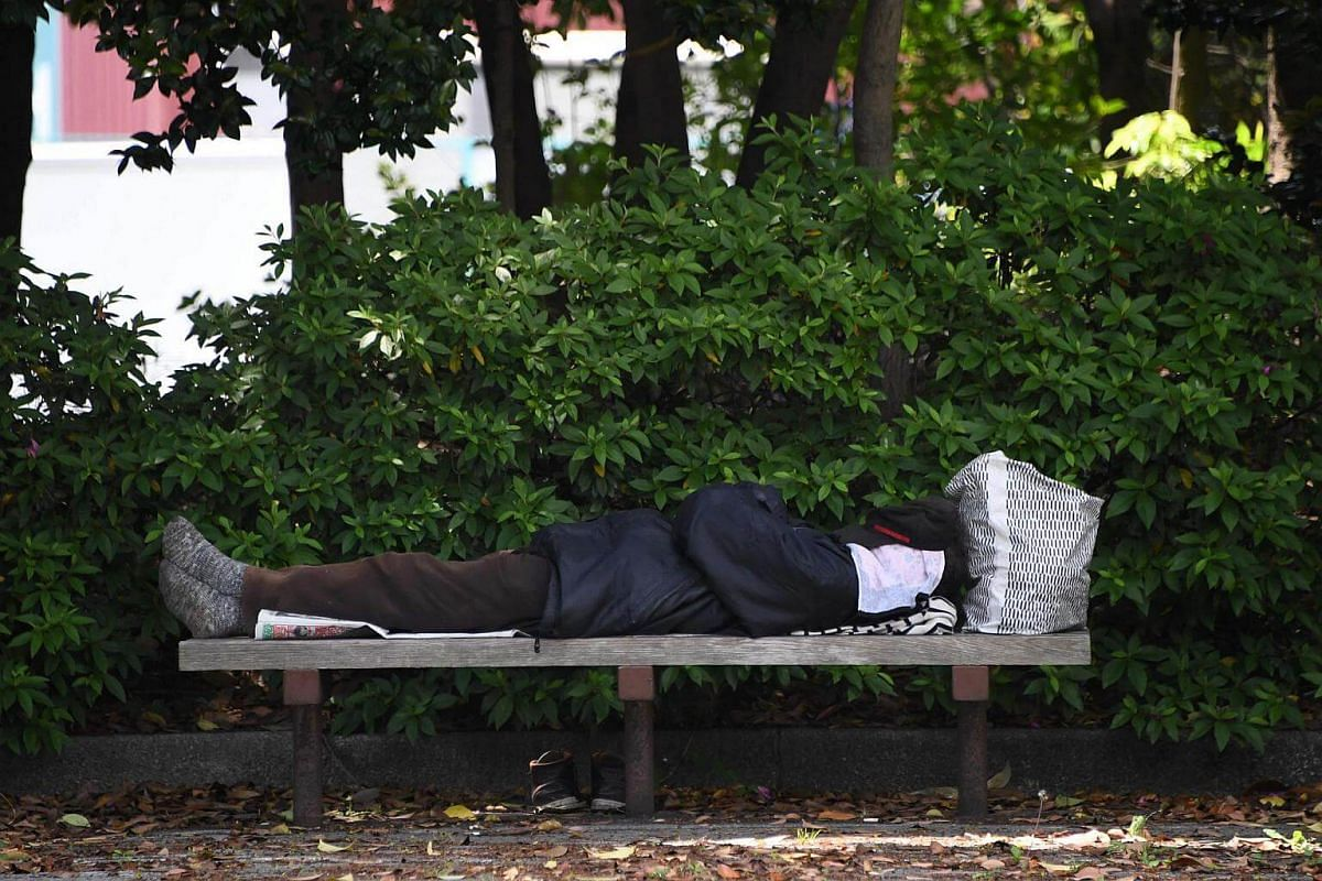 A homeless man sleeps on a bench at a park in Tokyo on Thursday (May 18).