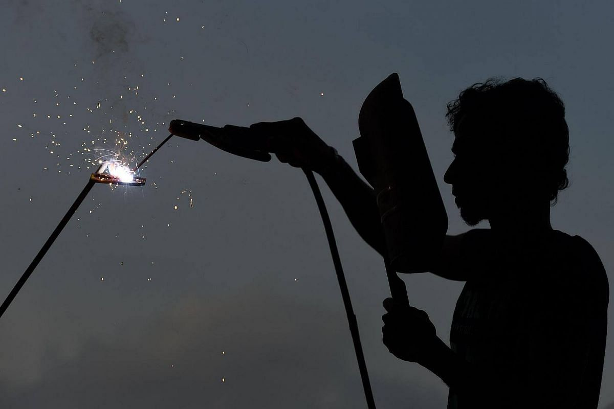 A Sri Lankan ironworker welds material at a building site in Colombo on Wednesday (May 17).