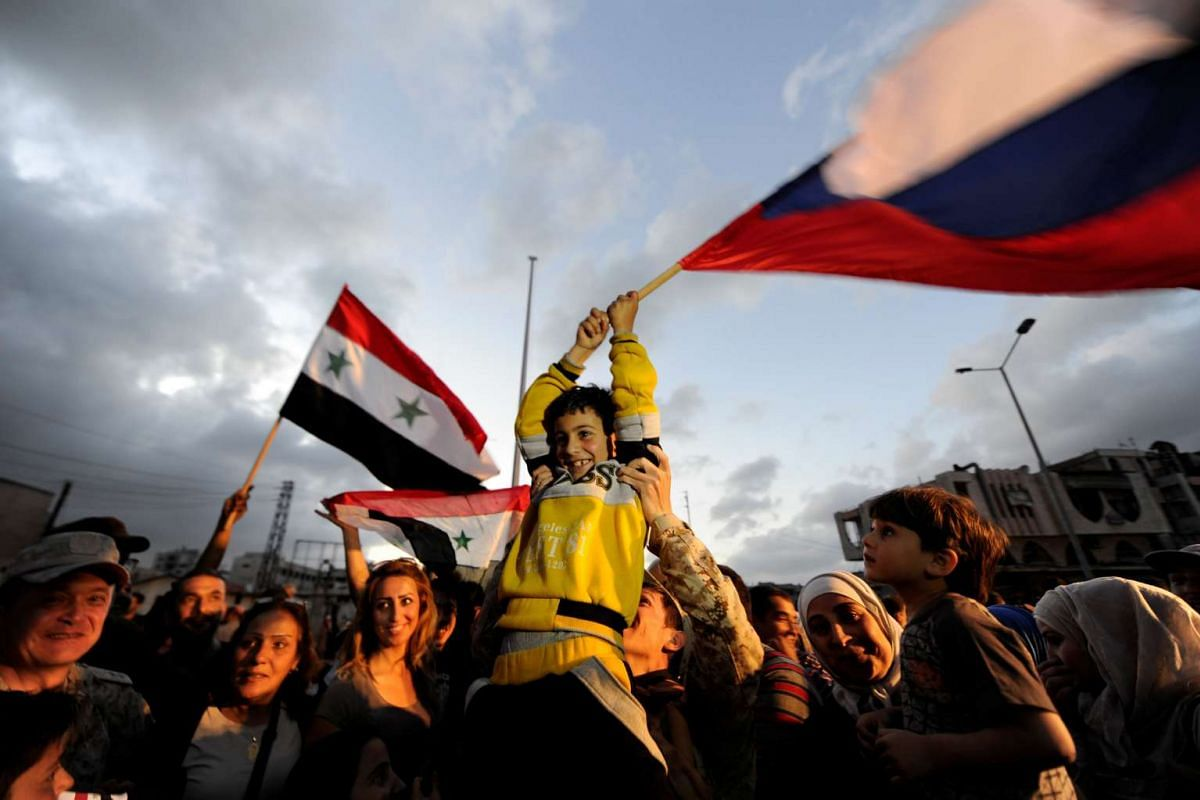 People celebrate carrying a Russian and Syrian national flags inside Waer district, after rebel fighters and their families evacuated the besieged Waer district in the central Syrian city of Homs, after an agreement was reached between rebels and Syr