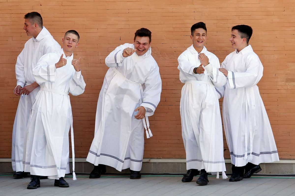 Altar boys wait to see Pope Francis outside the church of the Parish of San Pier Damiani at Casal Bernocchi on the southern outskirts of Rome, Italy May 21, 2017. PHOTO: REUTERS