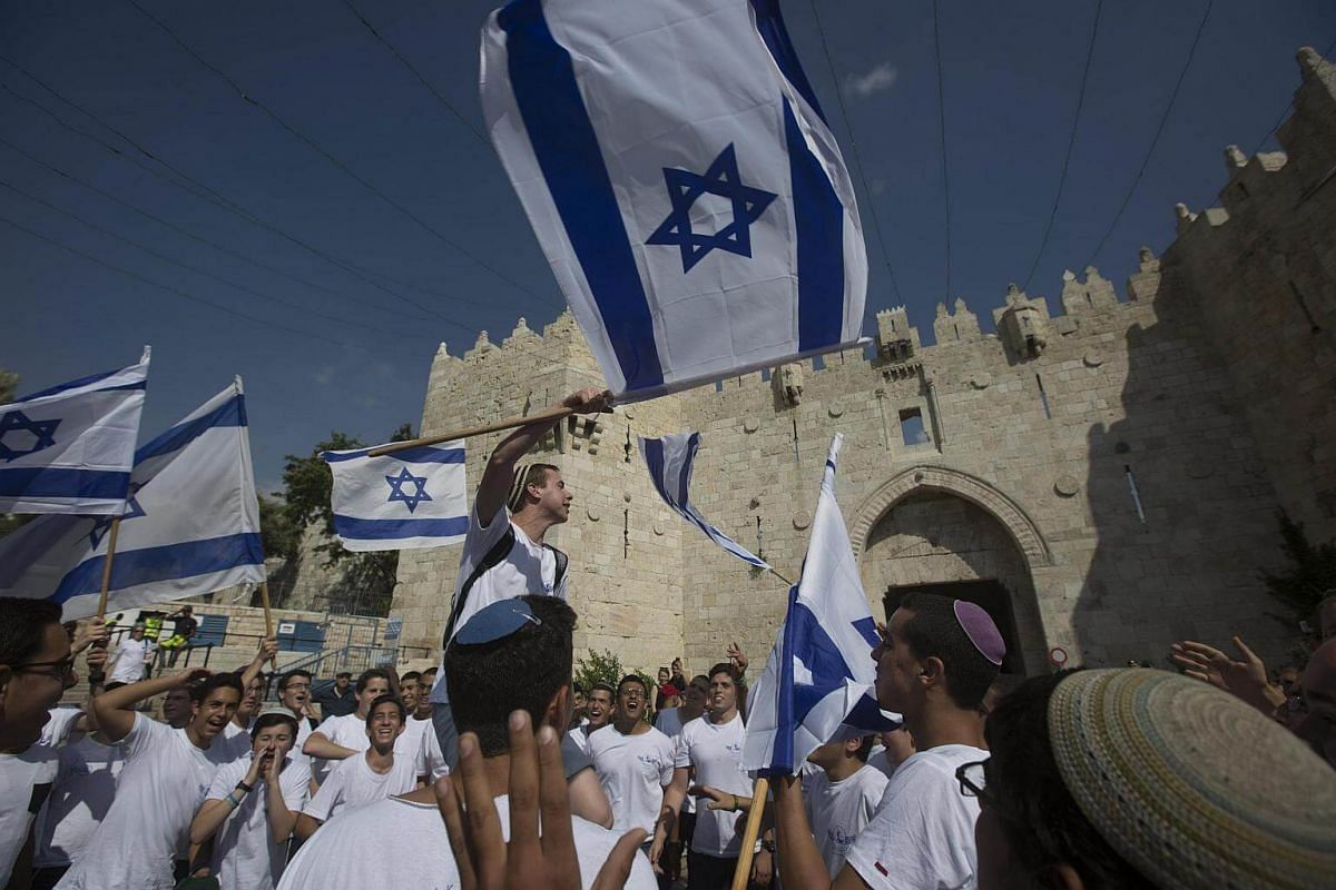 Israeli Far right wing activists wave flags at the Damascus gate of Jerusalem's Old City, during the Israeli right wing march marking the Jerusalem Day.