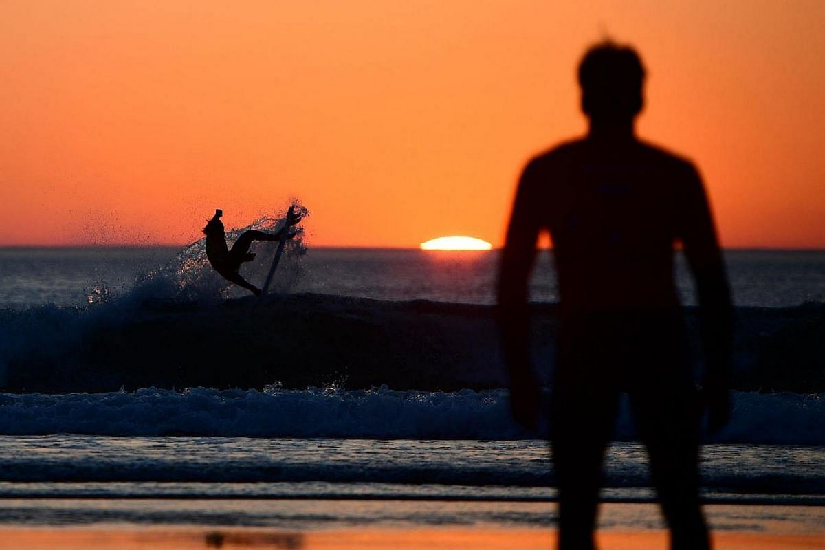 A surfer competes during the heat 76 - Round 2 as the sun sets in Biarritz, southwestern France, during the 2017 ISA World Surfing Games.