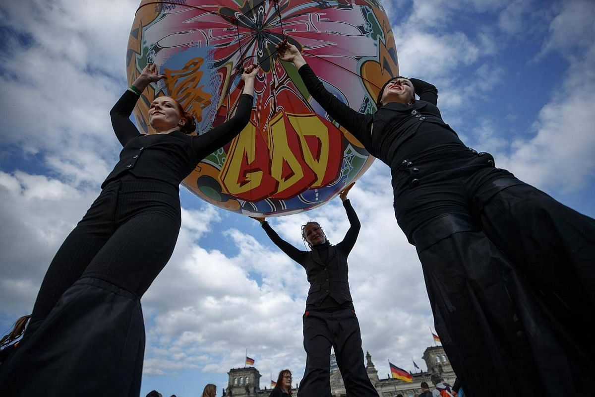 Artists hold a balloon as they perform during the opening worship of the German Protestant Kirchentag (Church Day) in Berlin, Germany.