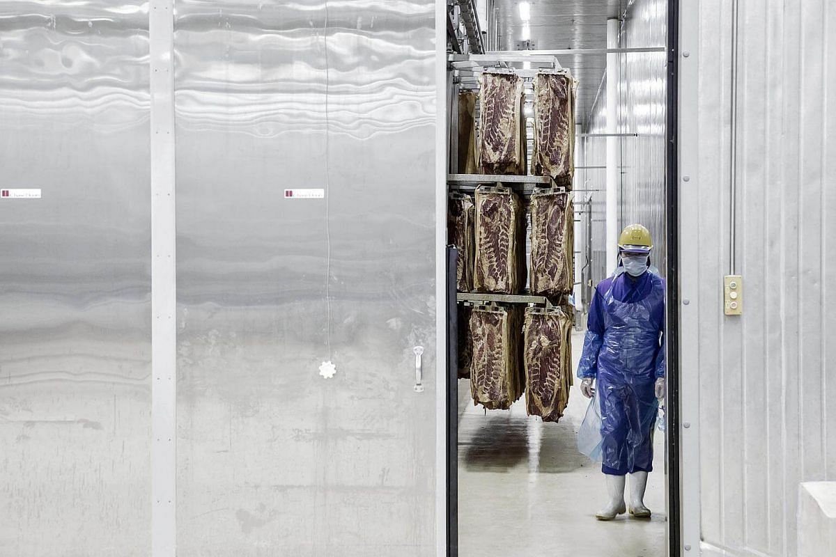 An employee stands near racks of imported Smithfield Foods Inc. pork bellies, which will be processed into bacon, at the WH Group Ltd. facility in Zhengzhou, China, on April 13, 2017.