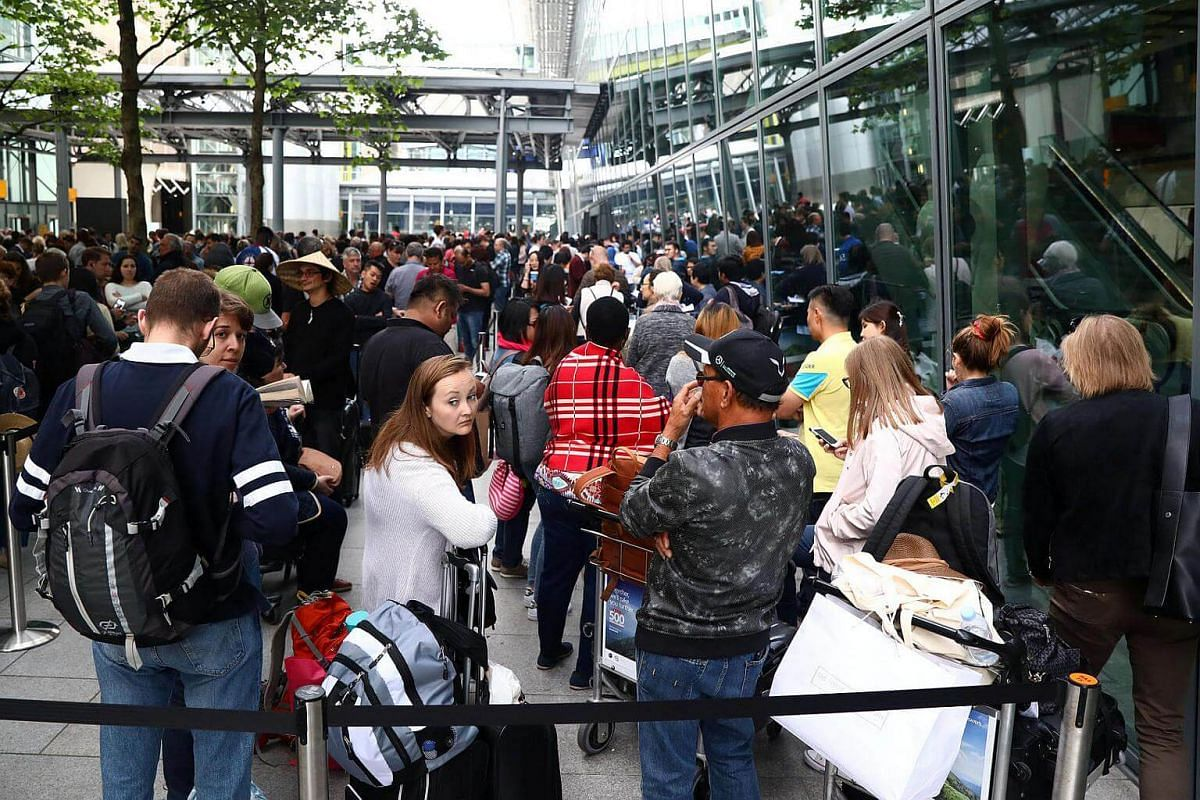 People queue with their luggage outside Heathrow Terminal 5 in London, Britain on May 28, 2017