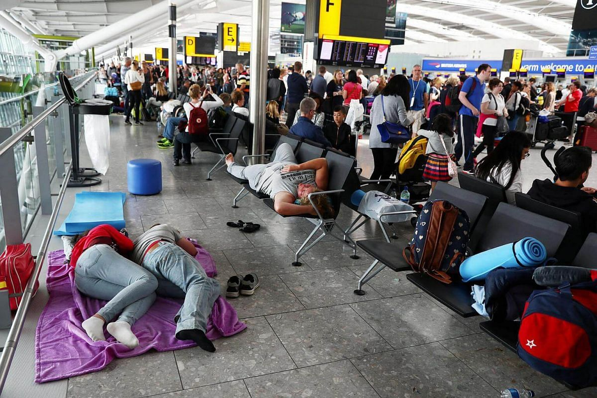 People sleep next to their luggage at Heathrow Terminal 5 in London, Britain on May 28, 2017.