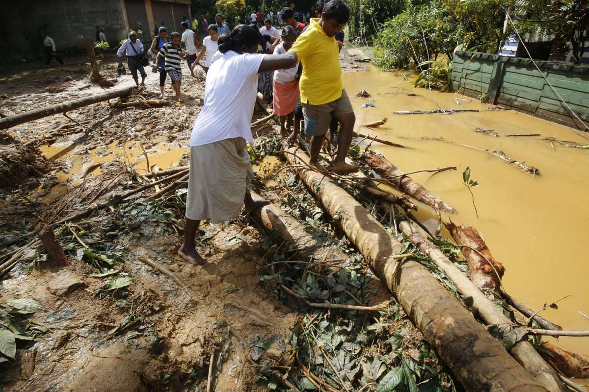 People walking over logs near the area where a landslide occured in which 35 people were feared killed at Athwelthote in Baduraliya, some 98 kilometers from Colombo, Sri Lanka, on May 28, 2017.