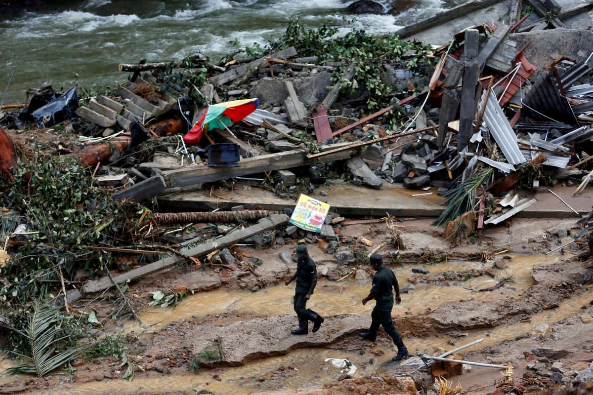 Sri Lankan army soldiers walking past the debris of houses at a landslide site during a rescue mission in Athwelthota village, in Kalutara, Sri Lanka on May 28, 2017.