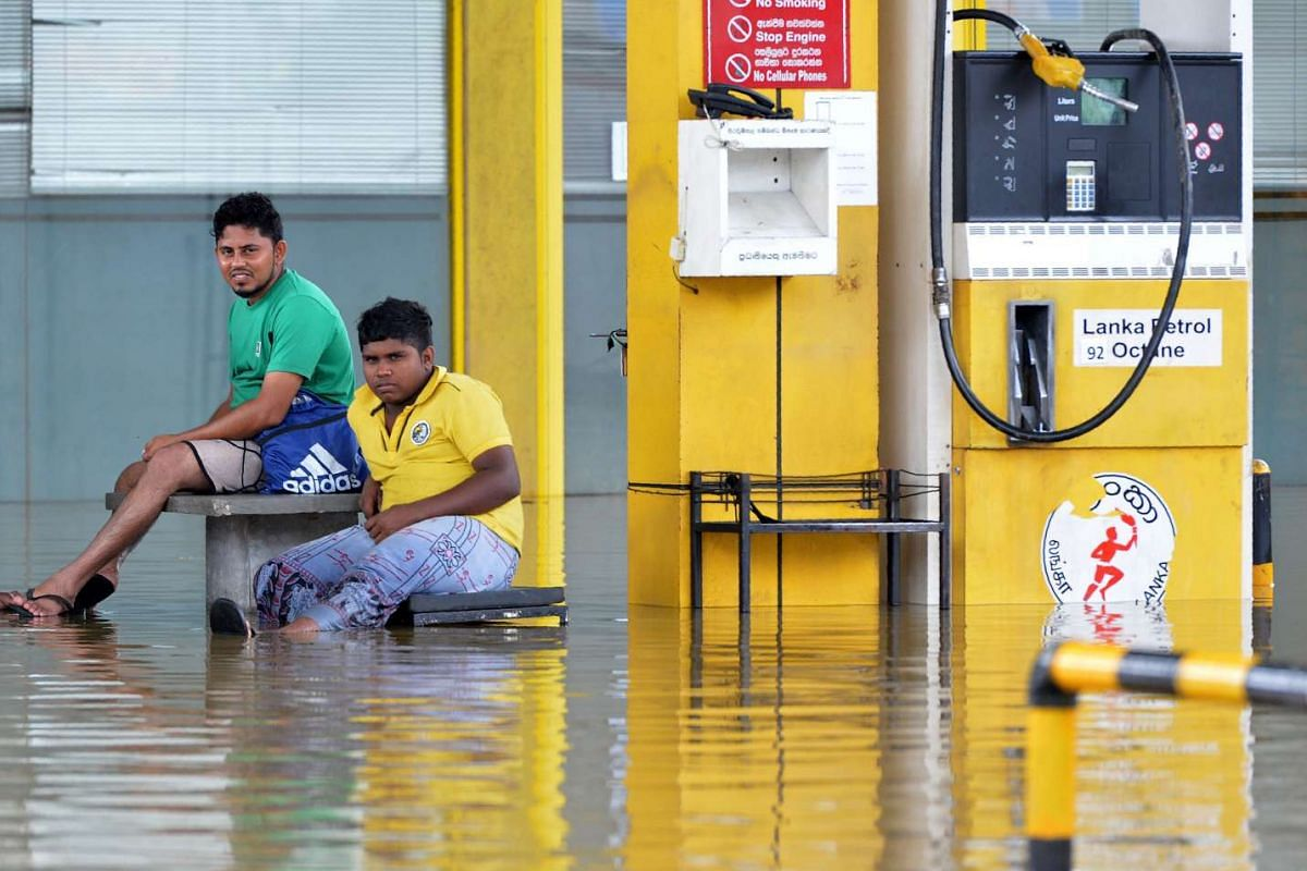 Sri Lankan gas station workers look over a flooded forecourt following rains in Kaduwela on May 27, 2017.