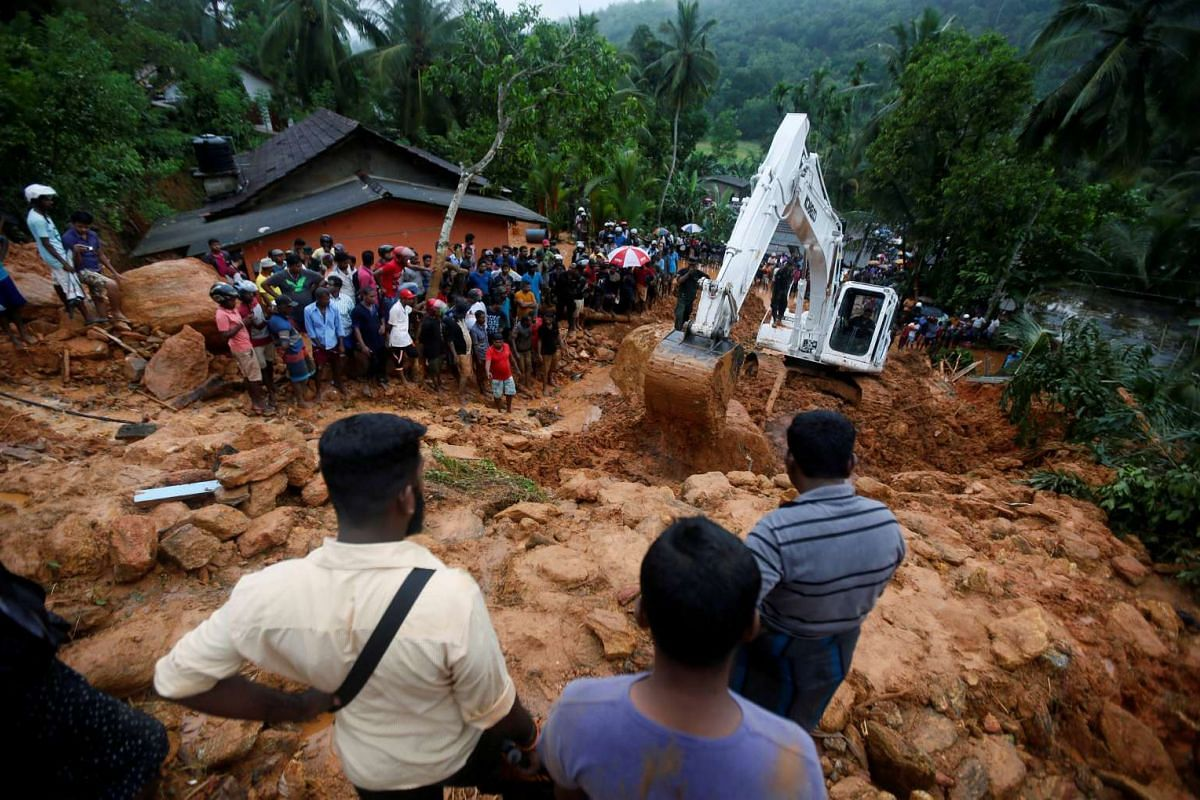 People gather during a rescue mission at the site of a landslide in Bellana village in Kalutara, Sri Lanka on May 26, 2017.
