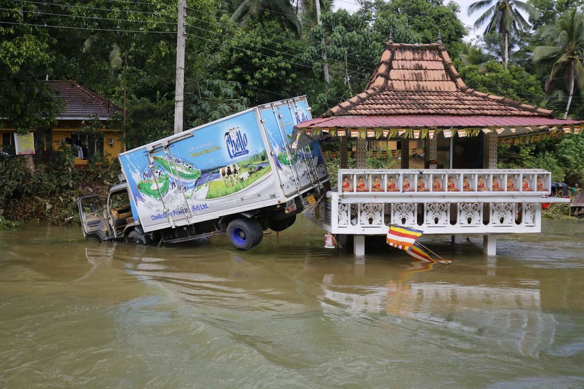A truck stuck next to a structure in flood waters at Athwelthote in Baduraliya, some 98 kilometers from Colombo, Sri Lanka, on May 28, 2017.
